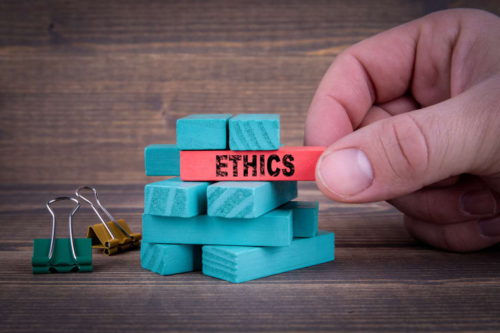 """Thumb and fingers pulling out a red block that reads """"Ethics"""" out of a stack of blocks."""