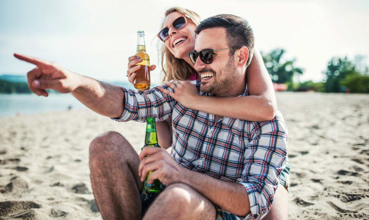 A man and woman drinking beer on the beach.