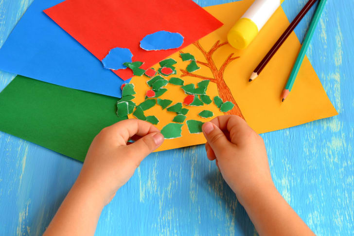 Child tears a red paper into small pieces. Child holds red paper pieces in his hands. Kindergarten art lesson. Set of color paper, pencils, glue stick on wooden background