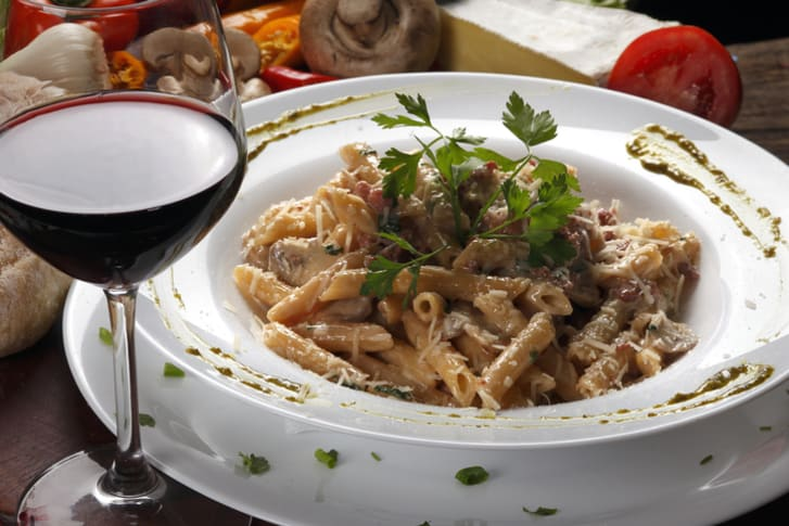 Plate of penne pasta and wine