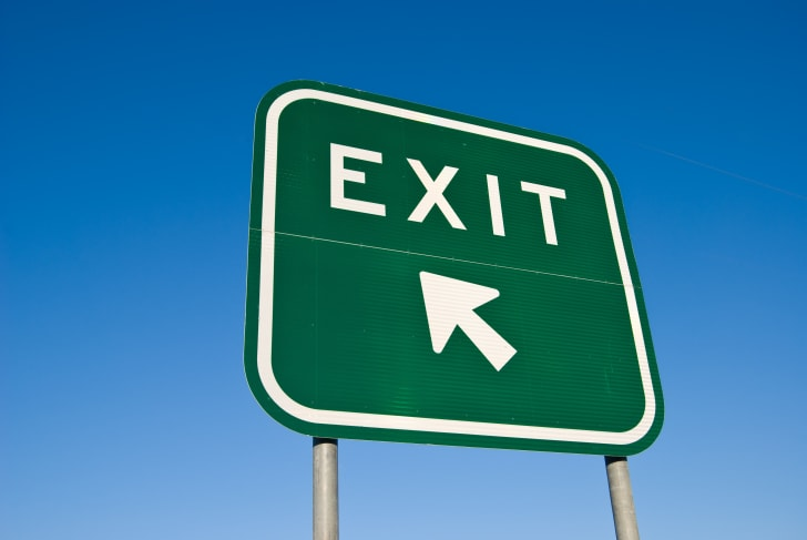 A green highway exit sign with white lettering