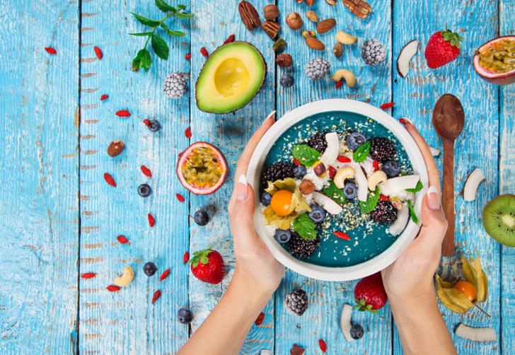 Smoothie bowl with fresh berries, nuts, seeds, fruit and vegetables
