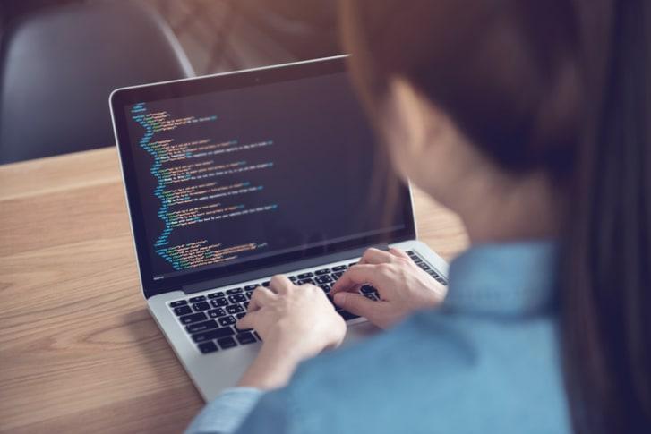Woman entering code onto a laptop computer