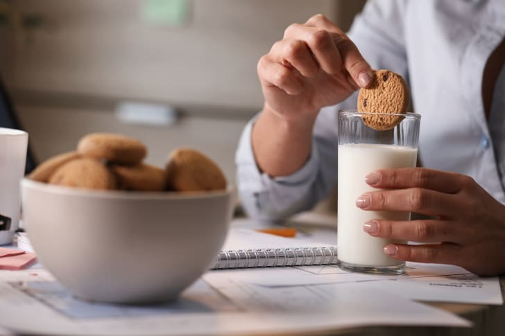 A woman dunks a cookie into a glass of milk