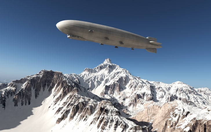 A blimp flying over snow-covered mountains