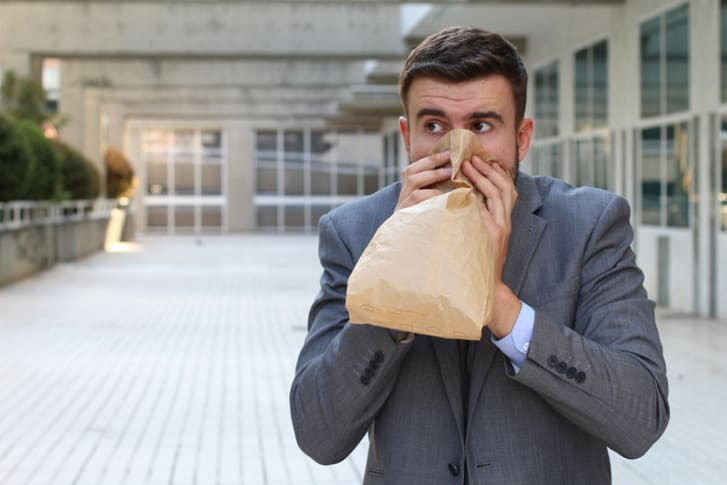 Stressed out man breathing into a paper bag