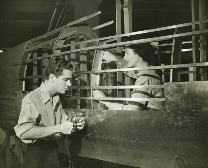 A young man and young woman build an airplane in a WWII-era factory