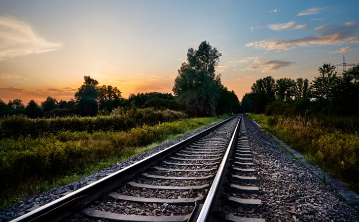 Train tracks in front of a forest at sunset