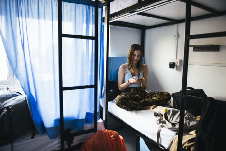 A young woman uses her cellphone at a hostel in India