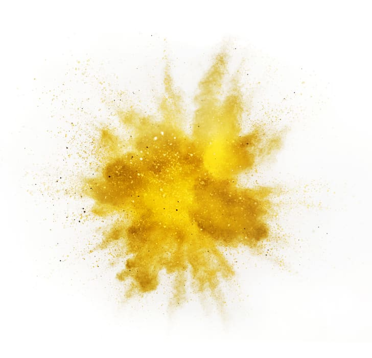Explosion of yellow powder against a white background