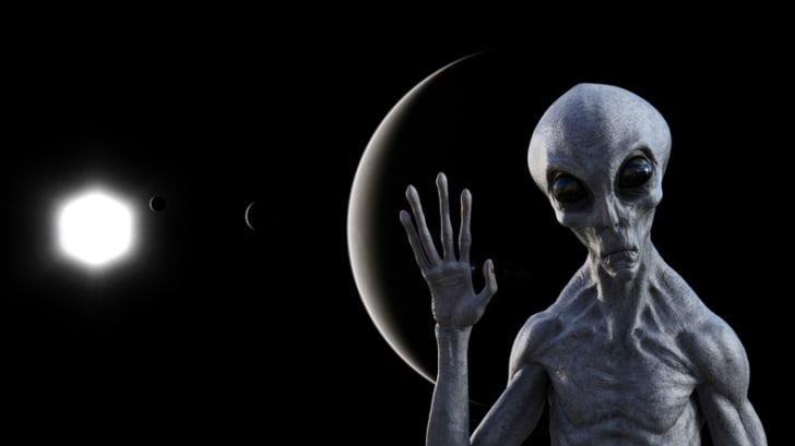 An illustration of an alien waving at the camera