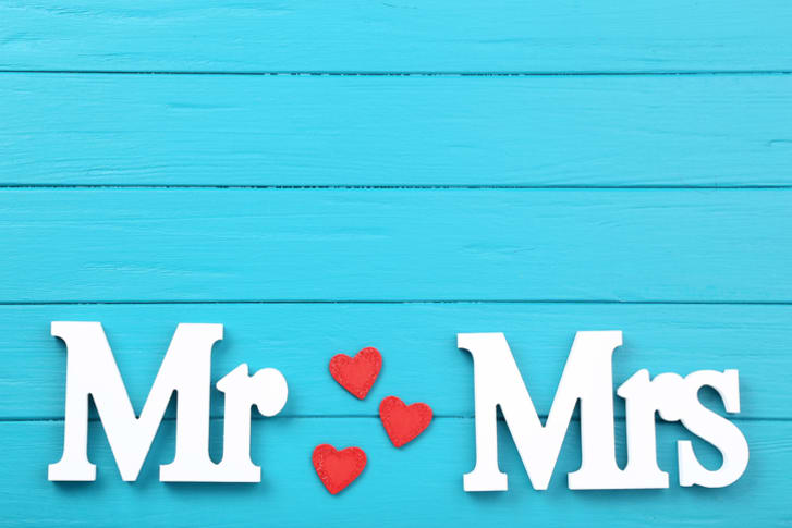 Words 'Mr.' and 'Mrs.' in white against a blue, wooden background