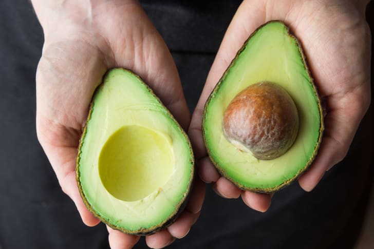 A woman holds up a freshly slice avocado