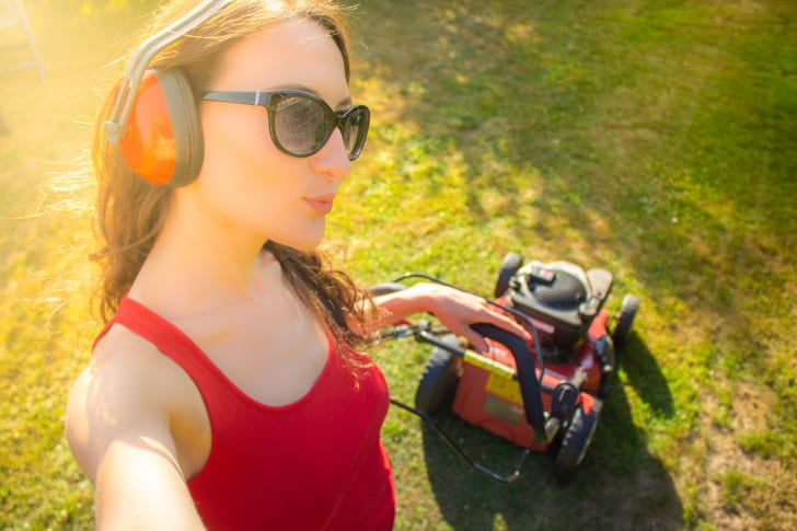 Young woman poses for selfie while mowing the lawn