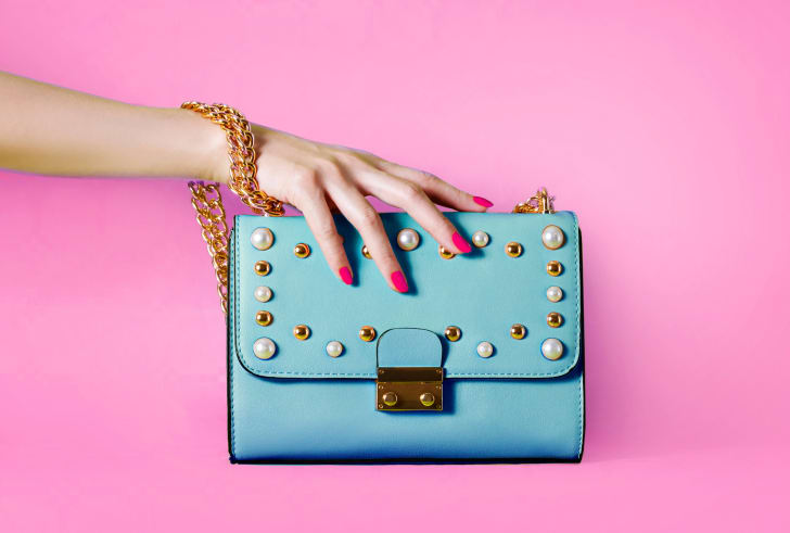 Sky blue handbag purse and beautiful woman hand with red manicure isolated on pink background