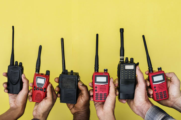 Group of hands holding portable two way radios with yellow background