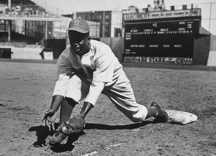 American baseball player Jackie Robinson (1919 - 1972) grounds a ball at first place while warming up for an exhibition game against the New York Yankees, Ebbets Field, NYC, 1950s