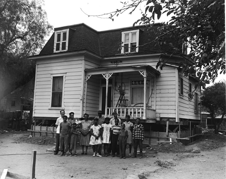 American baseball player Jackie Robinson (1919 - 1972) (Back row, 4th from right), wearing a military uniform, stands with members of his family outside of a house, possibly in Georgia, c. 1942