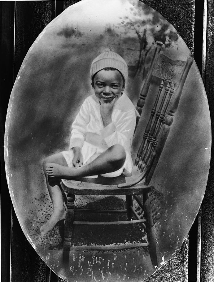 Oval shaped portrait of a American baseball player Jackie Robinson (1919-1972) as a young boy sitting on a chair, circa 1925