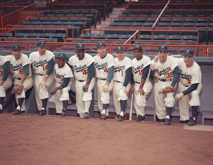 Portrait of members of the Brooklyn Dodgers baseball team pose in the dugout, 1954