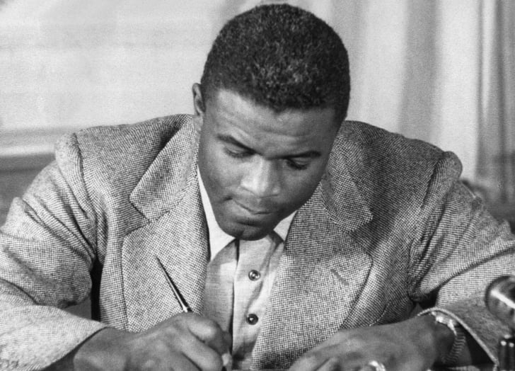 Undated photo of US baseball star Jackie Robinson as he signs a then-record contract to play for the Brooklyn Dodgers