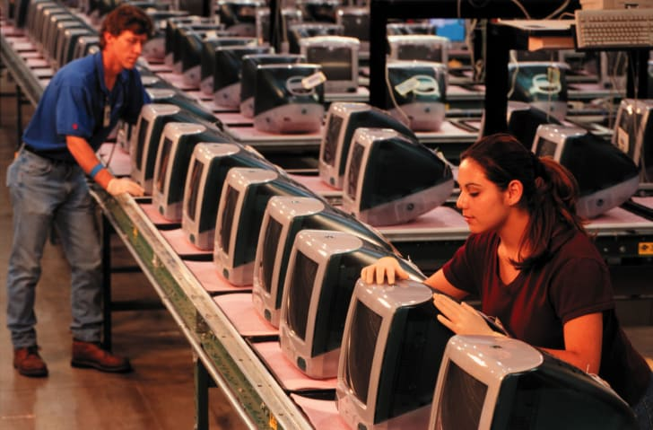 Workers setting up Apple iMacs in 1999.