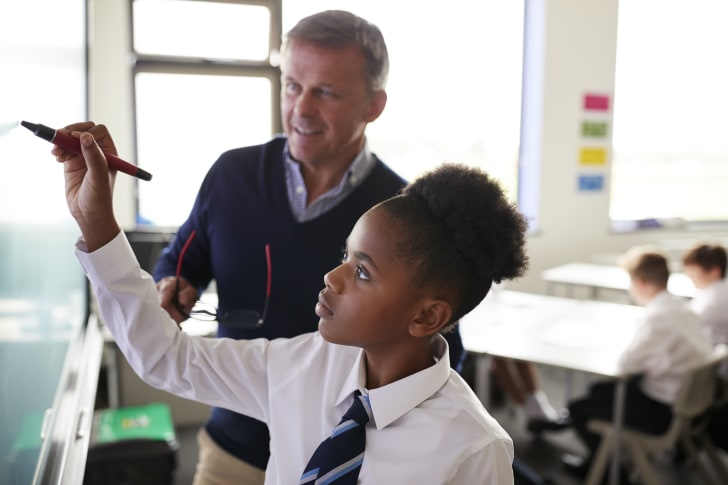 A teacher with a student near a whiteboard.