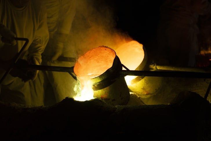 A worker pouring molten metal at a foundry.
