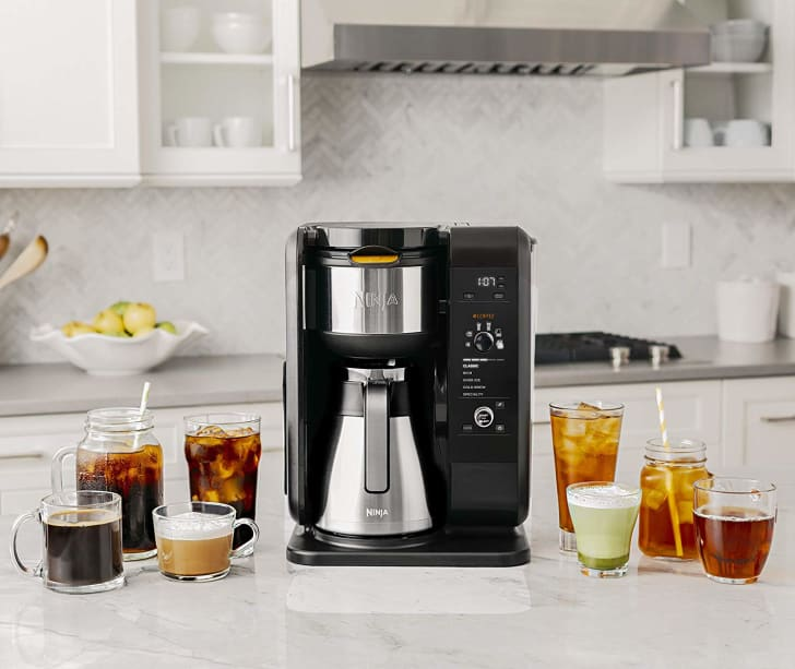 The Ninja Hot and Cold Brewed Coffee System on a countertop surrounded by beverages.