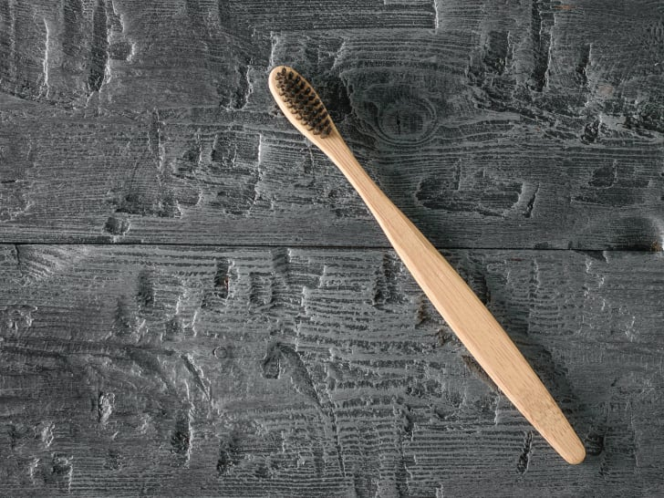 A brown toothbrush on a dark wooden table.