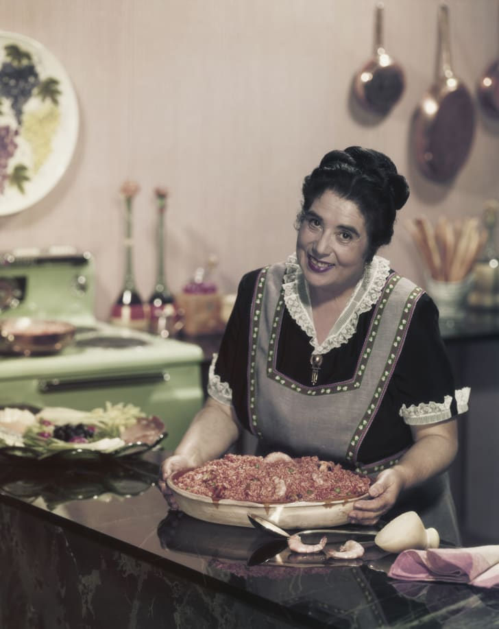 Woman prepares a meal in a vintage apron