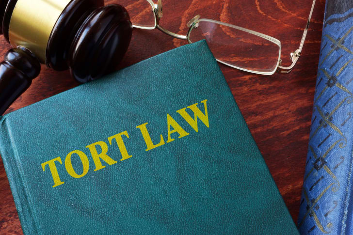 """An image of a book that reads """"tort law"""" on a table with glasses and a gavel."""