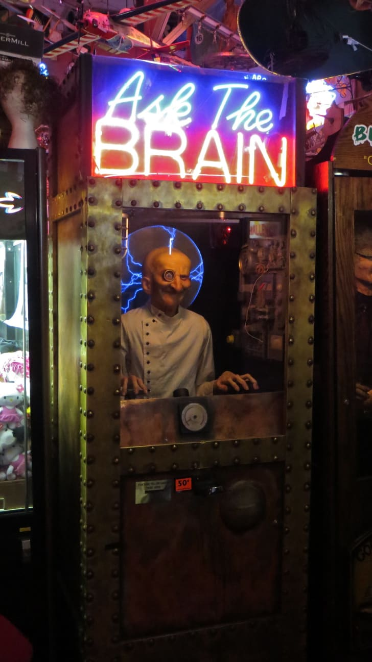 "An animatronic figure in a case with a sign above it saying ""Ask the Brain"" in Marvin's Marvelous Mechanical Museum."