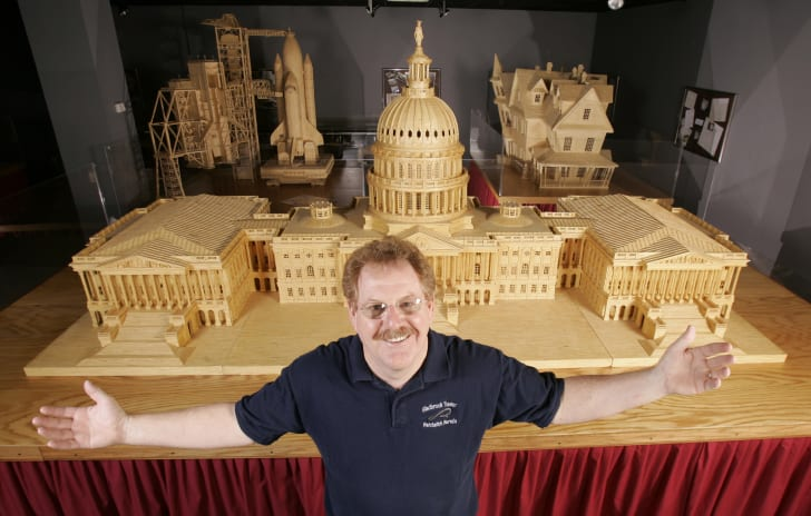 Pat Acton in front of a matchstick construction of the U.S. Capitol.