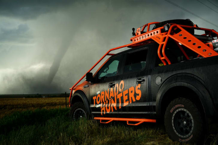 A reinforced vehicle is pictured near a tornado