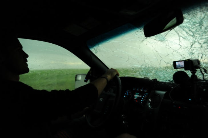 A storm chaser drives a car with a smashed windshield