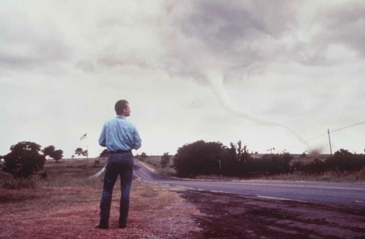 A publicity photo from the 1996 film 'Twister' depicts actor Bill Paxton looking at a tornado