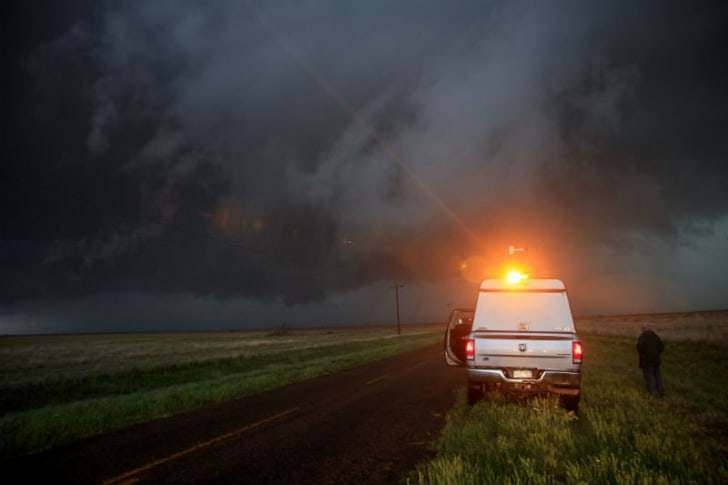 Support scientist Tim Marshall stands outside of a vehicle to observe a supercell thunderstorm in Lamb County, Texas in May 2017