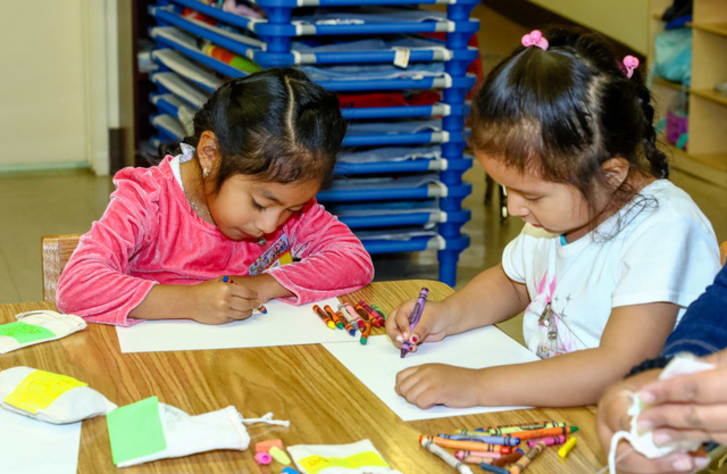 Children drawing with crayons in class.