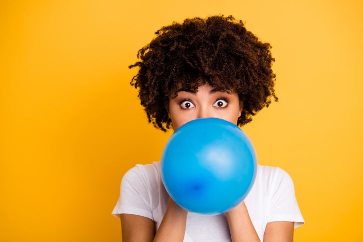 Young woman blowing up a blue balloon against a yellow background