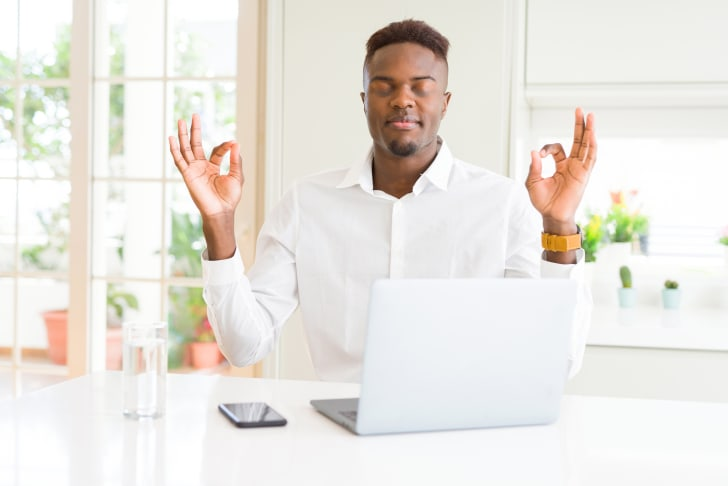 Man takes a break from work to meditate at his laptop