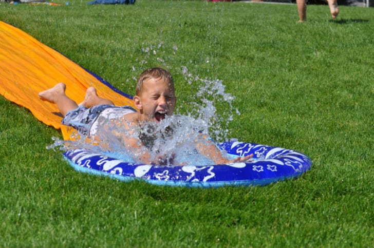 A child goes down a water slide