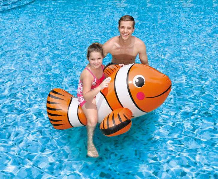A girl sits on a clownfish-shaped float next to her dad in a pool.