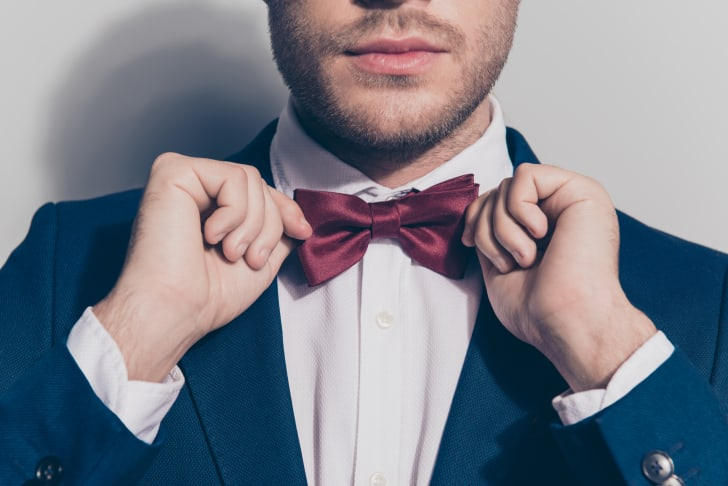 A man ties a bow tie