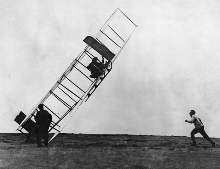 Orville Wright (1871 - 1948) lands one of the early Wright gliders badly, overseen by his brother Wilbur (1867 - 1912)