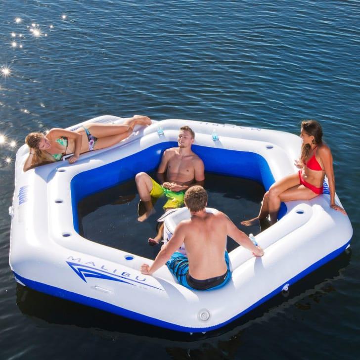 People sit on an Aquaglide Malibu Island