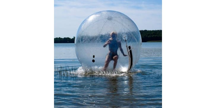 A person rolls across the surface of a lake in a giant ball.