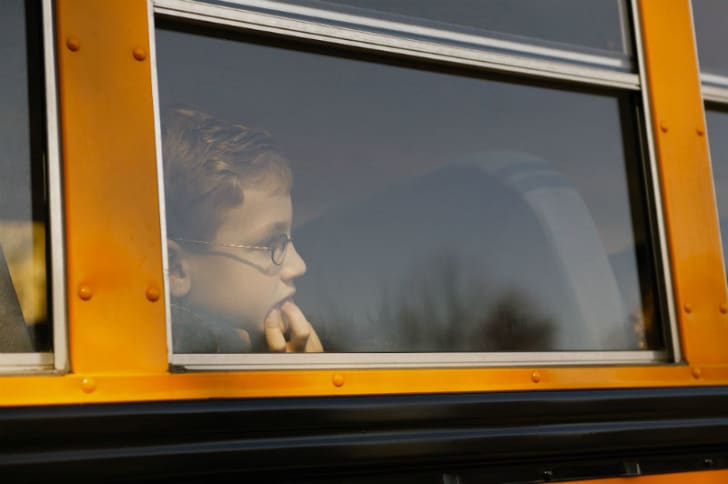A child looks out of a school bus window