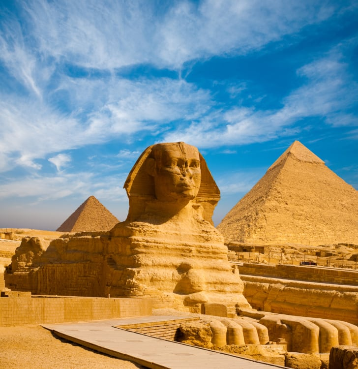 Full profile of Great Sphinx including pyramids of Menkaure and Khafre in the background on a clear sunny, blue sky day in Giza, Cairo, Egypt with no people