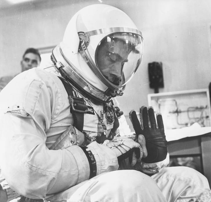Astronaut John W Young, co-pilot of the NASA Gemini 3 mission, inspecting his spacesuit at the Complex 16 suiting-up area, March 23rd 1965.